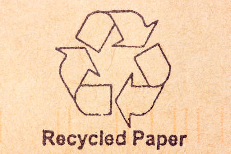 Brown recycled paper with black recycle symbol photo