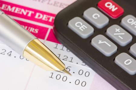 Metalen pen, rekenmachine en een loonstrook met maandloon