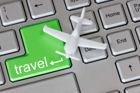 Plane  on keyboard with travel button, to illustrate online booking or purchase of plane ticket  photo