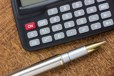 Adding up figures concept with modern calculator and pen on the table Stock Photo - 24389515