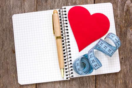 reforming: Establezca sus metas. Cinta de la medida, la pluma y el papel del coraz�n en el cuaderno.