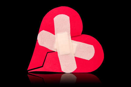 abandonment: Broken heart with plaster. Isolated on black background
