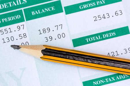 Potlood met de verklaring van de betaalde salarissen Stockfoto
