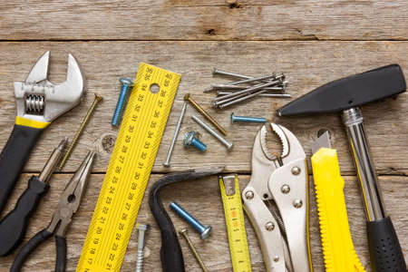 Assorted work tools on the wooden background photo