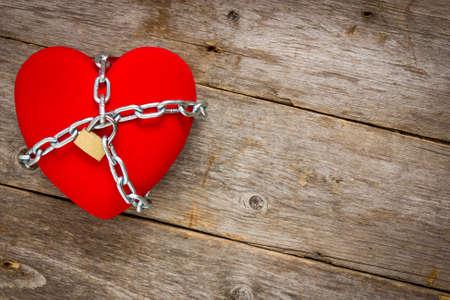 ラヴ ・ ロックダウン: 心の木製の背景に鎖を持つ図形 写真素材