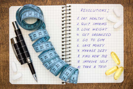 reforming: Resolutions written on a notepad with a measure tape and vitamin pills