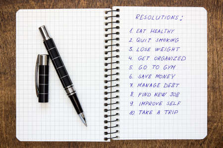 reforming: Spiral notebook with list of resolutions on the wooden table Stock Photo