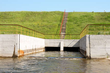 hydroelectricity: Water flowing over floodgates of a small dam Stock Photo