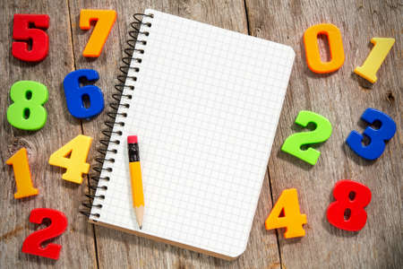 Colorful plastic numbers and empty notebook with pencil photo