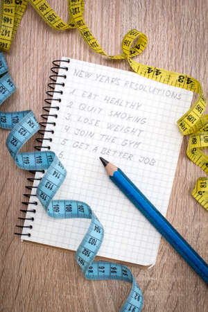 reforming: Measure tape and  notepad with New Years resolutions