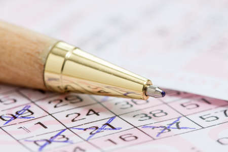 ballpen: Wooden ballpen and lotto ticket with chosen numbers Stock Photo