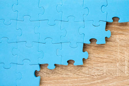 merge together: Blue puzzle on wooden background.Teamwork concept