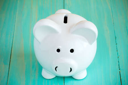 piggy: White piggy bank on the blue wooden background