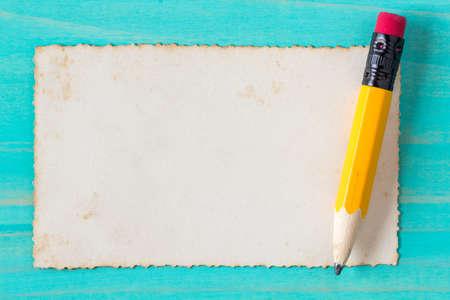 lapiz y papel: Lápiz de color amarillo con el papel viejo en la superficie de madera azul Foto de archivo
