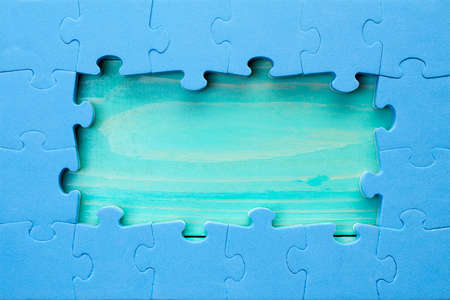 Blue jigsaw puzzle pieces arranged as a border around a green wooden surface