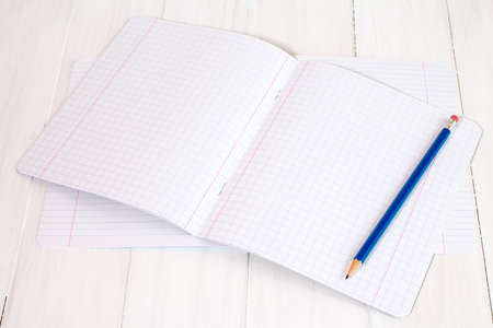 books on a wooden surface: New exercise books and pencil on white wooden surface