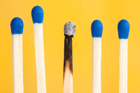 combustible: Four matches and one burnt on yellow background Stock Photo