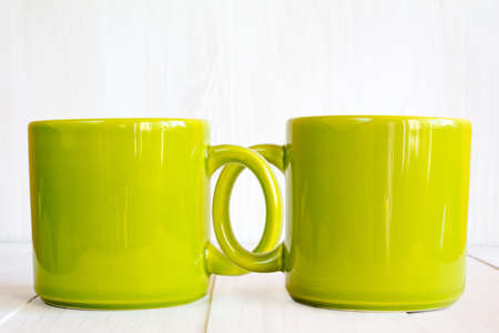 coupled: Two coupled coffee mugs on wooden background Stock Photo