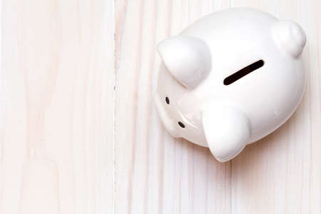 Piggy bank on the white wooden background, top view