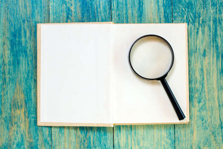 closer: Open book and magnifier on blue wood surface