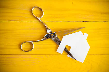 tijeras: Tijeras y casa cortan de papel sobre el fondo amarillo