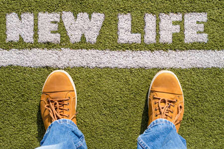 Mans legs behind the white line from above with New Life sign Stock Photo
