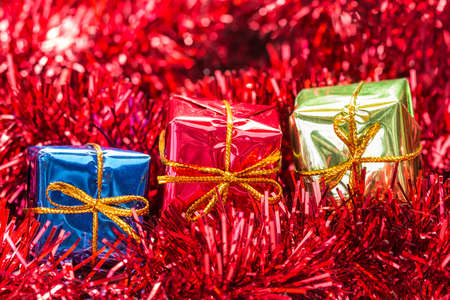 three gift boxes: Three gift boxes on red tinsel, close-up view Foto de archivo