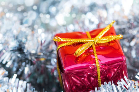 the tinsel: Christmas decoration with silver tinsel and red gift box Stock Photo