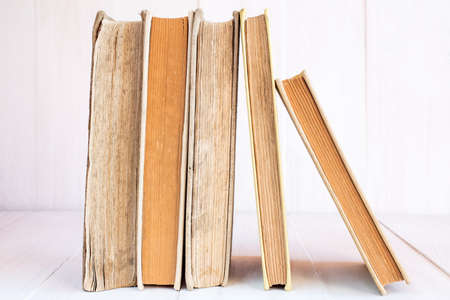 books library: Old books in a row on wooden background