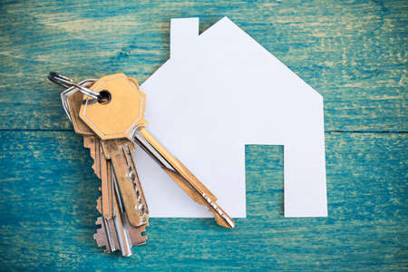 House icon and keys on wooden background 스톡 콘텐츠