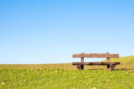 진정 장소는 휴식과 휴식을 취할 수 있습니다. 앉아서 휴식하는 등산객 또는 캐주얼 워커를 기다리는 고요한 푸른 하늘 위에 빈 나무 벤치.