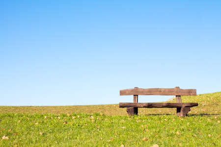 wooden bench: A calm place to rest and relax. An empty wooden bench  over a serene blue sky waiting for a hiker or casual walker to sit and rest.