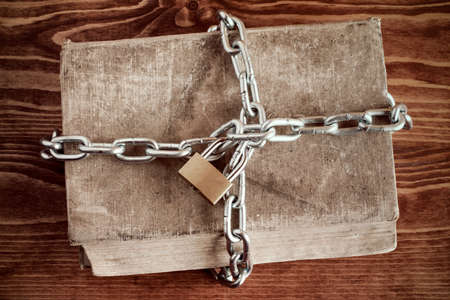 lock and chain: Old book with chain and padlock on wooden table Stock Photo