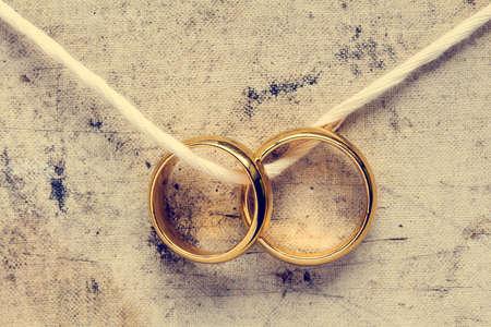 aniversario de boda: Los anillos de boda colgando de la cuerda. Imagen de la vendimia.