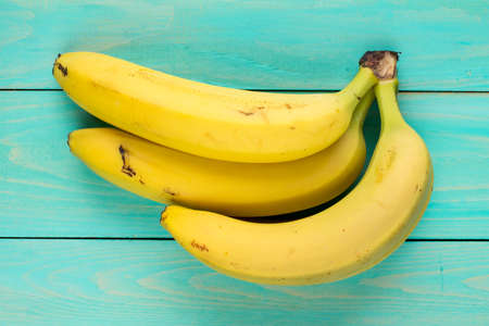 Bunch of bananas on wooden background. Top view.