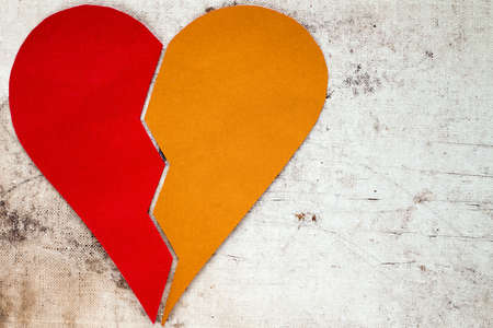 heart break: Red and yellow parts of the broken heart made of paper