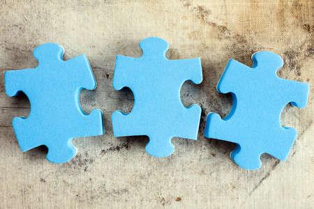 pacto: Tres piezas de un rompecabezas de color azul en el fondo del lienzo viejo Foto de archivo