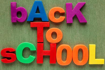 oracion: Sentencia Volver a la escuela en letras de pl�stico de colores sobre fondo verde Foto de archivo