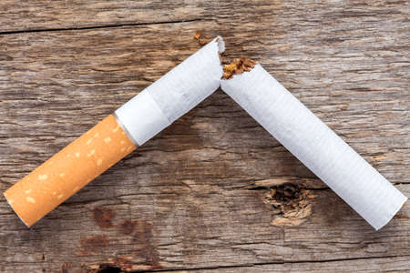 fumando: Close-up of broken cigarette on wooden background (Quit smoking today).