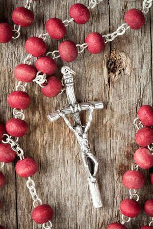 catholic symbol: Catholic rosary on old wooden texture background Stock Photo