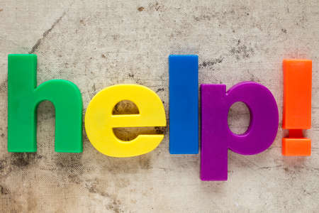 and spelling: Letter magnets spelling word HELP on dirty background Stock Photo
