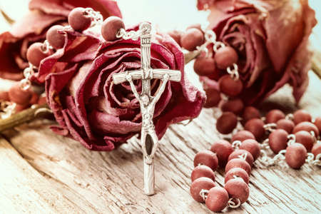 jesus rose: Catholic rosary and dry roses on old wooden background