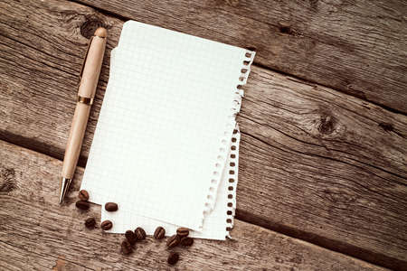 recipe background: Coffee beans with notebook and pen on wood background
