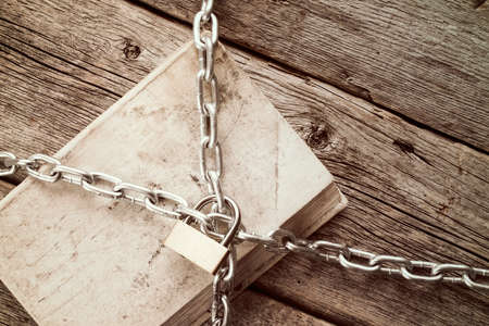 censor: Old book with chain and padlock on wooden background.Vintage style.