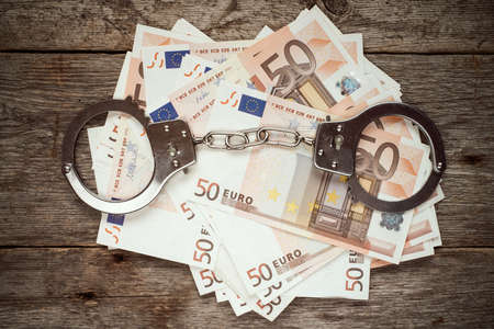 corruption: Handcuffs on euro banknotes, corruption or bribery concept Stock Photo