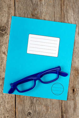 exercise book: Blue exercise book and glasses on the wooden background Stock Photo
