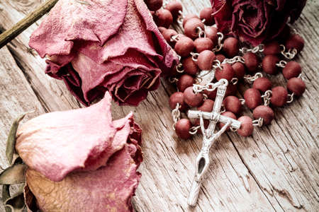 Catholic rosary and faded roses on old wooden background