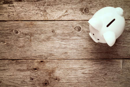 Piggy bank on the old wooden background, top view Banco de Imagens