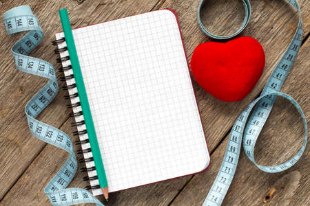 reforming: Measure tape,pen,red heart and blank notebook for your resolutions