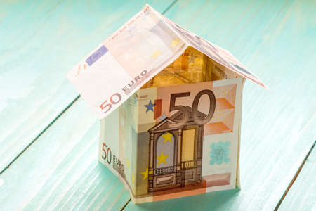 house exchange: House made of Euro banknotes on a wooden background
